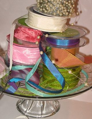 A tower of ribbon on a cake stand, reminds me of well, cake.